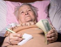 Alte Frau, die im Bett liegt Stockbilder