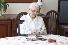 Alte Frau, die im Wohnzimmer am Tisch und in den Blicken an den alten Fotografien sitzt Stockfotos