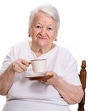 Alte Frau, die Kaffee- oder Teeschale genießt lizenzfreie stockbilder