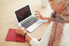 Alte Frau, die Laptop mit leerem Bildschirm verwendet stockfotos