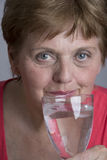 Alte Frau, die Mineralwasser trinkt Stockfoto