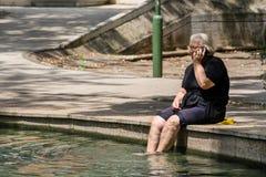 Alte Frau, die mit den Beinen im gesunden Mineralwasser sitzt Stockbild