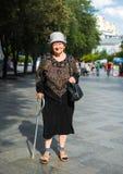 Alte Frau, die mit einem Stock geht Lizenzfreie Stockbilder
