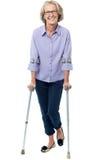 Alte Frau, die mit Krücken geht Lizenzfreie Stockfotografie
