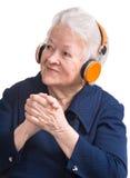 Alte Frau, die Musik in den Kopfhörern hört stockfoto