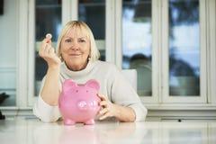 Alte Frau, die piggybank und Euromünze zeigt Lizenzfreie Stockfotografie