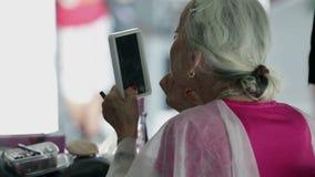 Alte Frau, die sich verschönert