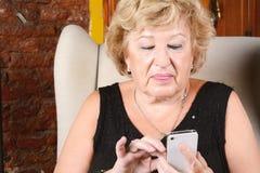 Alte Frau, die am Telefon schreibt Stockbilder