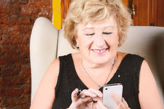 Alte Frau, die am Telefon schreibt Lizenzfreies Stockfoto
