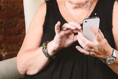 Alte Frau, die am Telefon schreibt Stockfoto