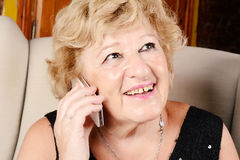 Alte Frau, die am Telefon spricht Stockbild