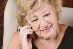 Alte Frau, die am Telefon spricht Stockfotografie