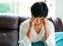 Alte Frau, die unter Kopfschmerzen, Druck, Migräne, Gesundheitsproblemkonzept leidet stockbild
