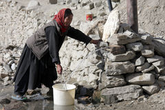 Alte Frau, die Wasser von einer Vertiefung nimmt Lizenzfreies Stockbild