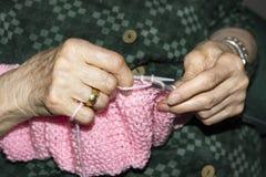 Alte Frau, die zu Hause strickt stockfotografie