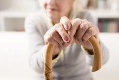 Alte Frau, die an zum Spazierstock hält stockbilder