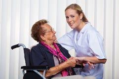 Alte Frau in einem Rollstuhl und in einer Krankenschwester Stockfotografie