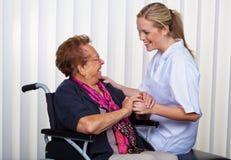 Alte Frau in einem Rollstuhl und in einer Krankenschwester Stockbilder