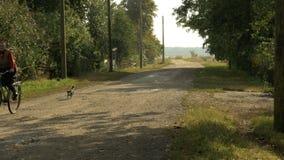 Alte Frau fährt auf das Fahrrad mit ihrem Hund stock footage