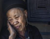 Alte Frau Hmong-Stammes, die innerhalb ihres Hauses in ihrem Dorf in Sapa, Vietnam sich entspannt Lizenzfreie Stockbilder