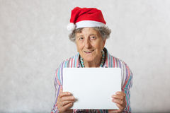 Alte Frau im Hut von einem Weihnachtsmann Lizenzfreies Stockfoto