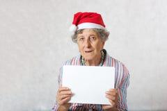 Alte Frau im Hut von einem Weihnachtsmann Stockfoto
