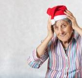 Alte Frau im Hut von einem Weihnachtsmann Lizenzfreies Stockbild