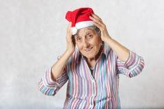 Alte Frau im Hut von einem Weihnachtsmann Lizenzfreie Stockfotos