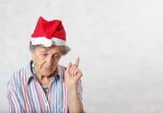 Alte Frau im Hut von einem Weihnachtsmann Stockfotos
