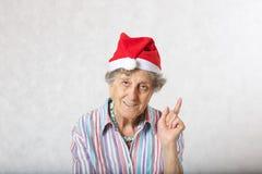 Alte Frau im Hut von einem Weihnachtsmann Lizenzfreie Stockbilder