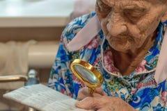 alte Frau mit dem Vergrößerungsglas, das versucht, von einer Zeitung zu lesen die Großmutter 90 Jahre alt liest am Tisch mit Verg stockfotografie
