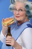 Alte Frau mit einem Burger und einem Bier Stockbild