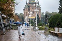 Alte Frau mit einem Regenschirm gehend auf ikonenhafte Victory Square Piata Victorei Lizenzfreie Stockfotografie