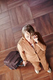 Alte Frau mit Gepäck am Telefon Stockfoto