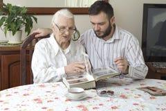 Alte Frau mit ihrem Enkel, der am Tisch im Wohnzimmer und in den aufpassenden alten Fotos sitzt Lizenzfreie Stockfotografie