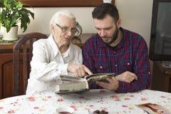 Alte Frau mit ihrem Enkel, der am Tisch im Wohnzimmer und in den aufpassenden alten Fotos sitzt Stockfoto
