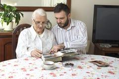 Alte Frau mit ihrem Enkel, der am Tisch im Wohnzimmer und in den aufpassenden alten Fotos sitzt Lizenzfreies Stockbild