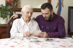 Alte Frau mit ihrem Enkel, der am Tisch im Wohnzimmer und in den aufpassenden alten Fotos sitzt Lizenzfreie Stockfotos