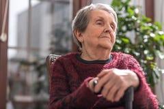 Alte Frau mit ihren Händen auf einem Stock Lizenzfreies Stockbild