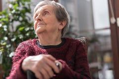 Alte Frau mit ihren Händen auf einem Stock Lizenzfreie Stockfotos