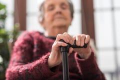Alte Frau mit ihren Händen auf einem Stock Stockfotos