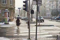 Alte Frau mit Regenschirmüberfahrtstraße Lizenzfreie Stockfotos