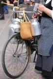alte Frau mit sehr alten Fahrrad- und Milchdosen Stockfotografie