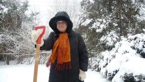 Alte Frau mit Spaten im Schnee Lizenzfreie Stockbilder