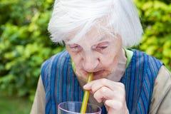 Alte Frau mit trinkendem Saft der Alzheimer Krankheit Himbeer lizenzfreie stockfotografie
