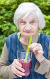Alte Frau mit trinkendem Saft der Alzheimer Krankheit Himbeer lizenzfreie stockbilder