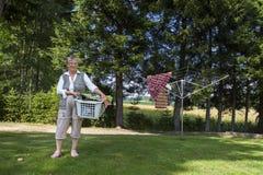 Alte Frau mit Wäschekorb Stockbild