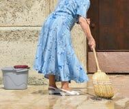 Alte Frau säubert den Bürgersteig Lizenzfreies Stockbild