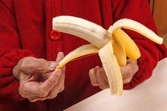Alte Frau säubert eine Banane Stockfotografie