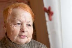 Alte Frau schaut heraus das Fenster Porträt Stockfotos